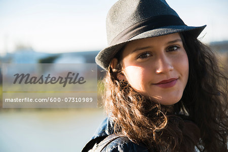 Close-up portrait of teenage girl outdoors, wearing fedora, smiling and looking at camera, Germany Stock Photo - Premium Royalty-Free, Image code: 600-07310989