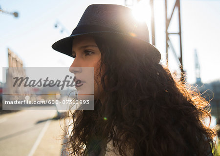 Close-up portrait of teenage girl outdoors, wearing fedora and looking into the distance, Germany Stock Photo - Premium Royalty-Free, Image code: 600-07310993