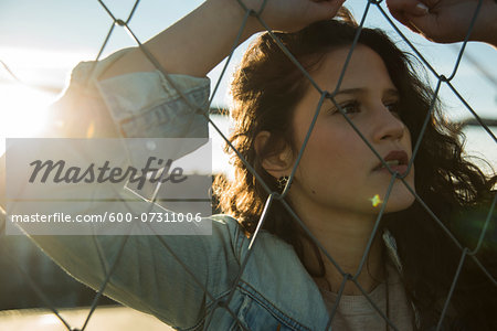 Close-up portrait of teenage girl standing outdoors next to chain link fence, Germany Stock Photo - Premium Royalty-Free, Image code: 600-07311006