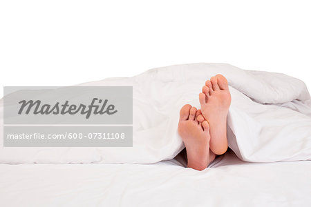 Bare feet sticking out of blanket on bed, studio shot on white background Stock Photo - Premium Royalty-Free, Image code: 600-07311108