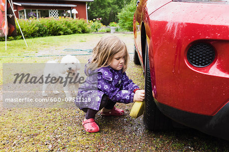 3 year old girl washing a red car while little white dog is watching, Sweden Stock Photo - Premium Royalty-Free, Image code: 600-07311119