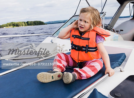 3 year old girl in orange life jacket sitting on top of motorboat, Sweden Stock Photo - Premium Royalty-Free, Image code: 600-07311130