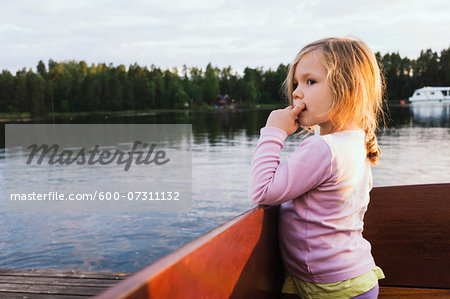 3 year old girl standing in a docked motorboat, looking at the lake, Sweden Stock Photo - Premium Royalty-Free, Image code: 600-07311132
