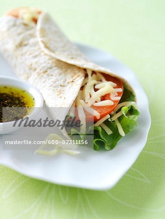 Vegetarian soft taco wrap with lettuce, tomato, and monterey jack cheese on a white plate with herbed olive oil on the side. Stock Photo - Premium Royalty-Free, Image code: 600-07311156