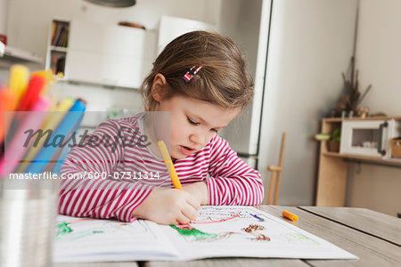 Girl Sitting at Table and Colouring Pictures Stock Photo - Premium Royalty-Free, Image code: 600-07311314