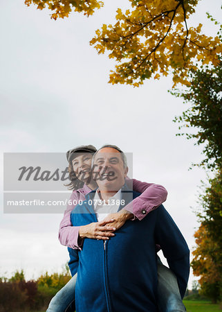 Man giving woman piggyback ride, Mannheim, Baden-Wurttemberg, Germany Stock Photo - Premium Royalty-Free, Image code: 600-07311388