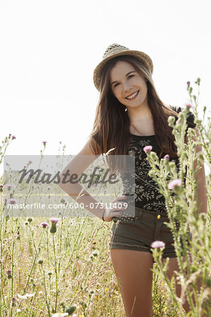Portrait of teenage girl wearing shorts and straw hat standing in field, smiling and looking at camera, Germany Stock Photo - Premium Royalty-Free, Image code: 600-07311409