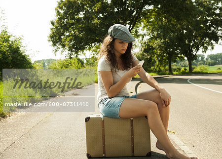 Teenage girl sitting on suitcase on the side of the road, looking at cell phone in summer, Germany Stock Photo - Premium Royalty-Free, Image code: 600-07311410