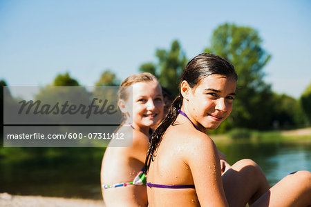 Close-up portrait of two girls sitting on beach at lake, looking over shoulder at camera and smiling, Lampertheim, Hesse, Germany Stock Photo - Premium Royalty-Free, Image code: 600-07311412