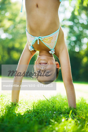 Close-up portrait of young girl doing a handstand on grass, Lampertheim, Hesse, Germany Stock Photo - Premium Royalty-Free, Image code: 600-07311413