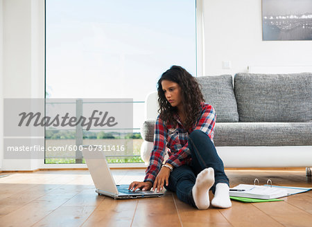 Teenage girl sitting on floor next to sofa, using laptop computer, Germany Stock Photo - Premium Royalty-Free, Image code: 600-07311416