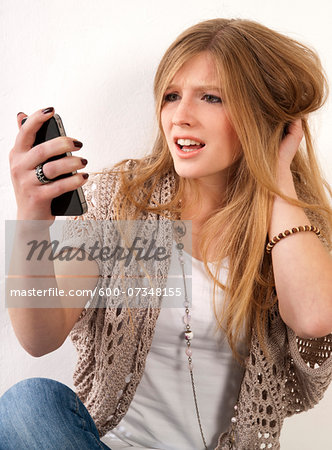 Young, blond, long-haired woman staring at cellphone with disbelief, studio shot on white background Stock Photo - Premium Royalty-Free, Image code: 600-07348155