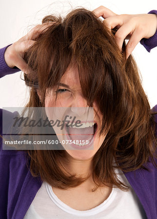 Close-up portrait of young, brown-haired woman screaming and looking at camera with hands in her hair, studio shot on white background Stock Photo - Premium Royalty-Free, Image code: 600-07348158
