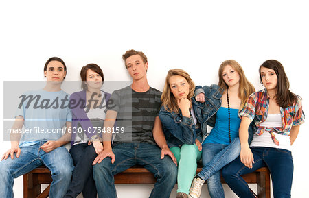 Portrait of six young people sitting together on a bench, studio shot on white background Stock Photo - Premium Royalty-Free, Image code: 600-07348159