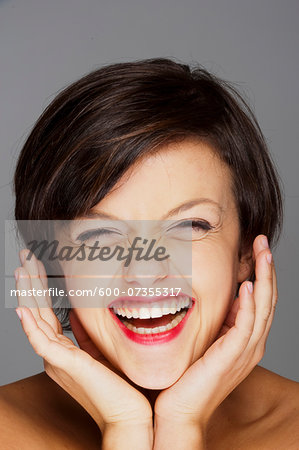 Head and Shoulders Portrait of Mid-Adult Woman Laughing with Grey Background Stock Photo - Premium Royalty-Free, Image code: 600-07355317