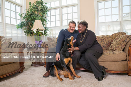 Mature Couple Petting Dog in Living Room at Home Stock Photo - Premium Royalty-Free, Image code: 600-07368540