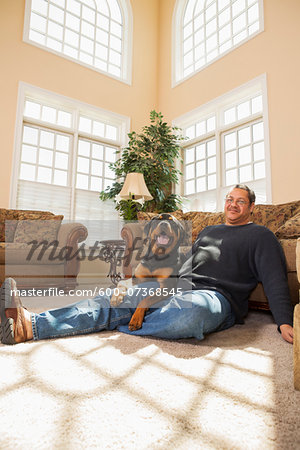 Portrait of Mature Man with his Pet Rottweiler in Living Room Stock Photo - Premium Royalty-Free, Image code: 600-07368545