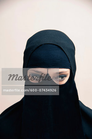 Close-up portrait of young woman wearing black, muslim hijab and muslim dress, eyes looking to the side showing eye makeup, studio shot on white background Stock Photo - Premium Royalty-Free, Image code: 600-07434926