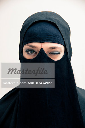 Close-up portrait of young woman wearing black, muslim hijab and muslim dress, winking and looking at camera, eyes showing eye makeup, studio shot on white background Stock Photo - Premium Royalty-Free, Image code: 600-07434927