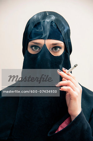 Close-up portrait of young woman wearing black, muslim hijab and muslim dress, holding cigarette and smoking, looking at camera, eyes showing eye makeup, studio shot on white background Stock Photo - Premium Royalty-Free, Image code: 600-07434930