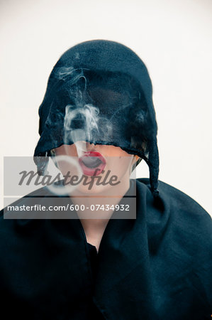 Close-up portrait of young woman wearing black, muslim dress and black, hijab covering part of head, while blowing smoke rings from red lips, studio shot on white background Stock Photo - Premium Royalty-Free, Image code: 600-07434932