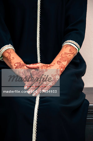 Woman sitting indoors with close-up of arms and hands painted with henna in arabic style, wearing a typical black, arabic, muslim dress, studio shot Stock Photo - Premium Royalty-Free, Image code: 600-07434933