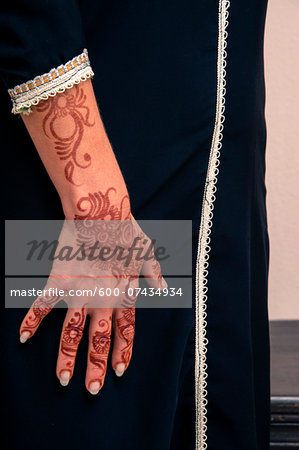Woman standing indoors, with close-up of arms and hand painted with henna in arabic style, wearing a typical black, arabic, muslim dress, studio shot Stock Photo - Premium Royalty-Free, Image code: 600-07434934