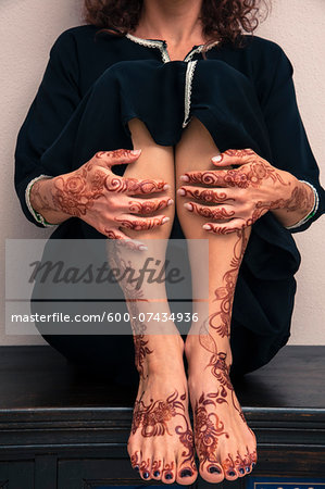 Low section of woman sitting indoors, showing legs, feet and hands painted with henna in arabic style, wearing a typical black, arabic, muslim dress, studio shot Stock Photo - Premium Royalty-Free, Image code: 600-07434936