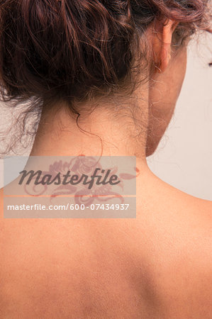 Close-up of woman's back and neck showing detail of henna painted tattoo in arabic style, studio shot on white background Stock Photo - Premium Royalty-Free, Image code: 600-07434937