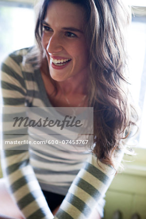 Portrait of young woman smiling and sitting in front of a window in a house, Portland, Oregon, USA Stock Photo - Premium Royalty-Free, Image code: 600-07453767
