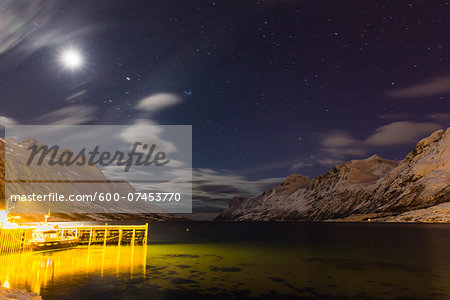 Boat and dock lit up at night with moon illuminating snow covered mountains at a fjord in the Arctic, Norway Stock Photo - Premium Royalty-Free, Image code: 600-07453770