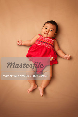 Portrait of Asian baby lying on back, wearing red dress, looking at camera and smiling, studio shot on brown background Stock Photo - Premium Royalty-Free, Image code: 600-07453952
