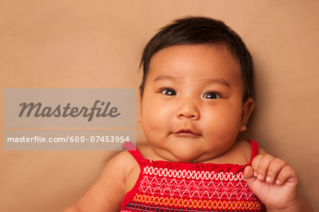 Close-up portrait of Asian baby lying on back, wearing red dress, looking at camera and smiling, studio shot on brown background Stock Photo - Premium Royalty-Free, Image code: 600-07453954
