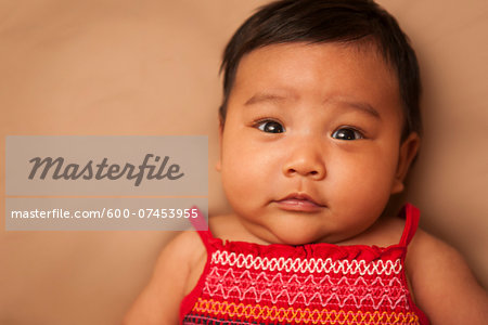 Close-up portrait of Asian baby lying on back, wearing red dress, looking at camera, studio shot on brown background Stock Photo - Premium Royalty-Free, Image code: 600-07453955