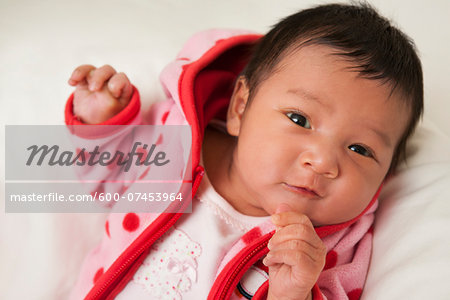 Close-up portrait of two week old Asian baby girl in pink polka dot jacket, smiling and looking at camera, studio shot Stock Photo - Premium Royalty-Free, Image code: 600-07453964