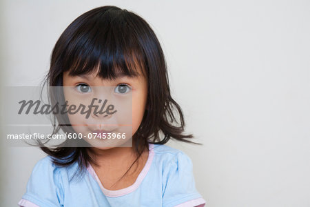 Close-up portrait of Asian toddler girl, looking at camera with surprised expression, studio shot on white background Stock Photo - Premium Royalty-Free, Image code: 600-07453966