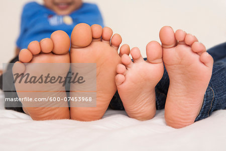 Brother and sister lying in bed together, close-up of the soles of their feet, studio shot Stock Photo - Premium Royalty-Free, Image code: 600-07453968
