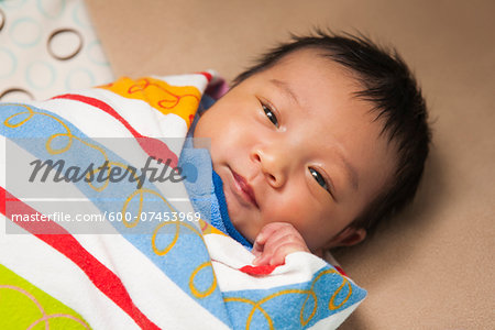 Close-up portrait of two week old, newborn Asian baby girl, wrapped in colorful swaddling blanket, studio shot Stock Photo - Premium Royalty-Free, Image code: 600-07453969