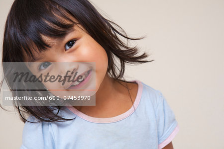 Close-up portrait of Asian toddler girl, looking at camera and smiling, studio shot on white background Stock Photo - Premium Royalty-Free, Image code: 600-07453970