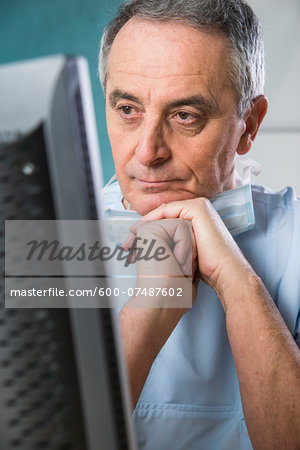 Close-up of Doctor with Sugical Mask at Computer Stock Photo - Premium Royalty-Free, Image code: 600-07487602