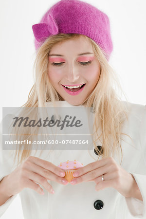 Close-up portrait of young woman wearing pink hat and holding cupcake, studio shot on white background Stock Photo - Premium Royalty-Free, Image code: 600-07487664