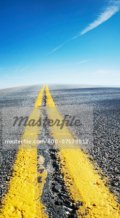 Close-up view of yellow center lines on deserted highway with blue sky, Canada Stock Photo - Premium Royalty-Free, Image code: 600-07529012