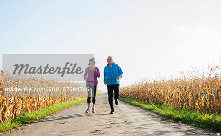 Adult couple running on country road, Germany Stock Photo - Premium Royalty-Free, Image code: 600-07584746
