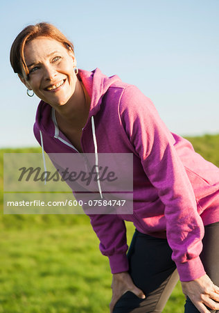 Close-up of mature woman taking a break from running outdoors, Germany Stock Photo - Premium Royalty-Free, Image code: 600-07584747