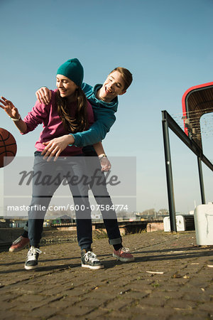 Teenage boy and girl playing basketball outdoors, industrial area, Mannheilm, Germany Stock Photo - Premium Royalty-Free, Image code: 600-07584774