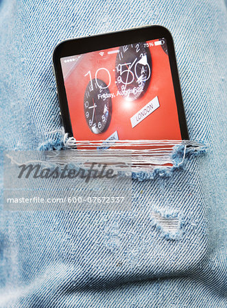 Close-up view of ripped pair of jeans with cell phone sticking out, Canada Stock Photo - Premium Royalty-Free, Image code: 600-07672337