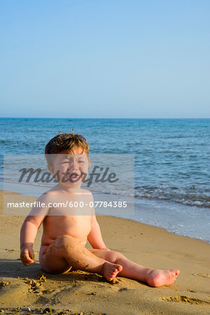Baby Boy Crying on Sand at Beach Stock Photo - Premium Royalty-Free, Image code: 600-07784385
