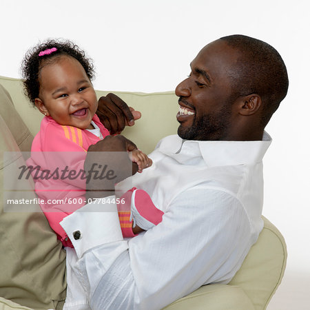 Portrait of Father and Baby Girl on Chair, Studio Shot Stock Photo - Premium Royalty-Free, Image code: 600-07784456