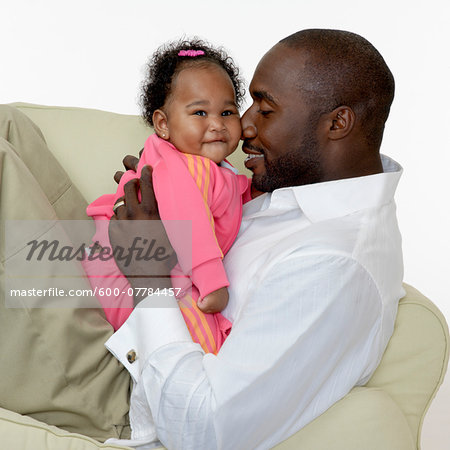 Portrait of Father and Baby Girl on Chair, Studio Shot Stock Photo - Premium Royalty-Free, Image code: 600-07784457