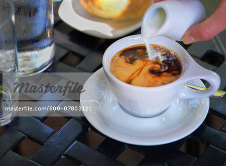 Cream being poured into coffee in white cup and saucer on outdoor, patio table, Canada Stock Photo - Premium Royalty-Free, Image code: 600-07803121